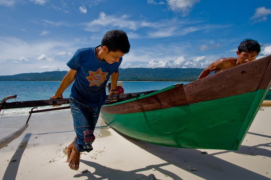 Two men haul a canoe onto the beach on a small island in Central Sulawesi.
