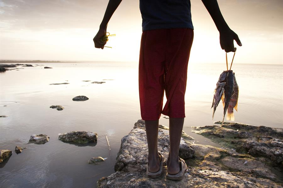 A young Ethiopian boy holds his fresh catch on the shores of Lake Langano, Ethiopia.