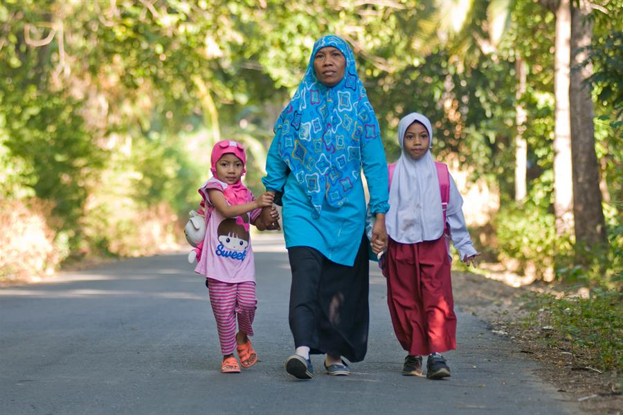 Woman and two girls walking along a road in Indonesia
