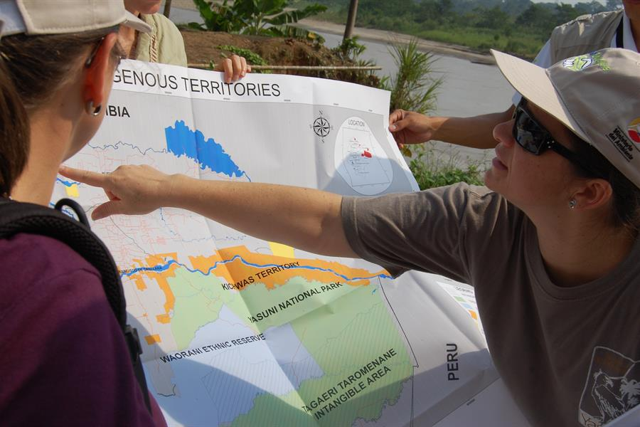 Group of people looking at a map of the Amazon rainforest in Ecuador