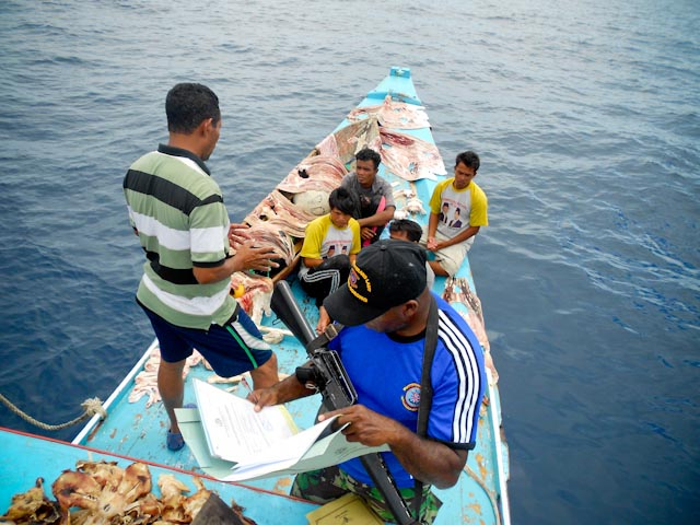 A Raja Ampat police officer reviews a fishing vessel's documents.