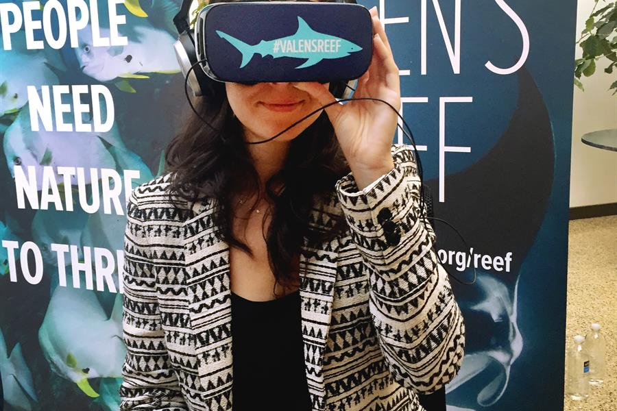 Woman wearing a VR headset promoting Valen's Reef