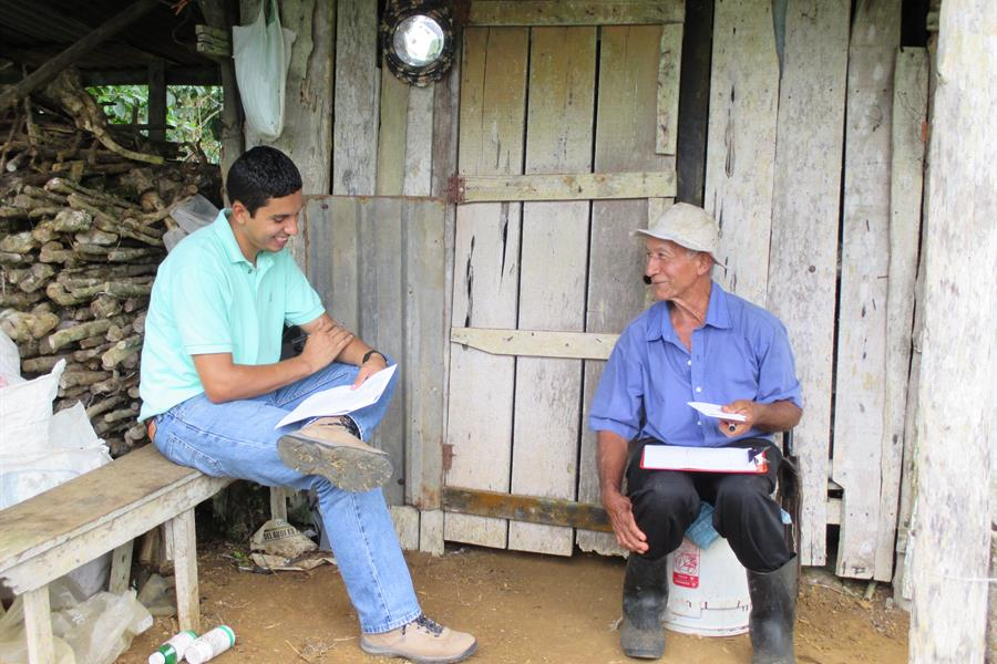 A coffee farmer answers survey questions as part of the CASCADE project.